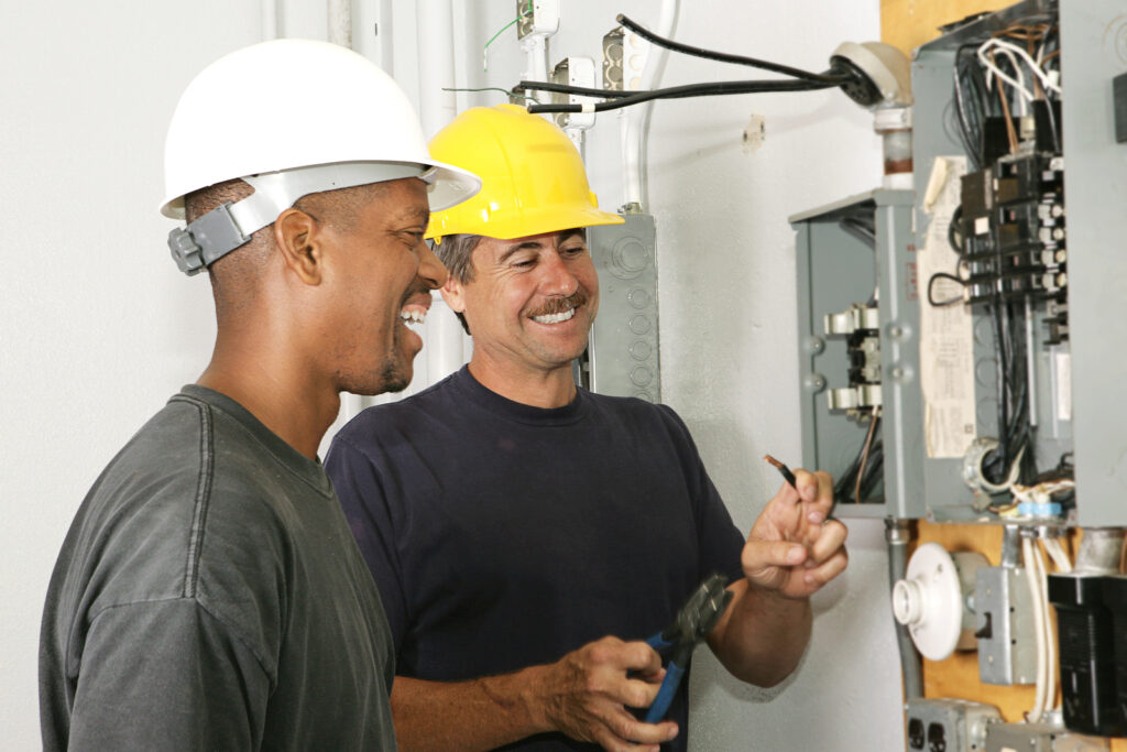 Two electricians working on an electrical panel together. Actual electricians performing work according to industry code and safety standards.
